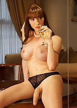 A Beautiful transsexual lady with a big cock shoving it into a champagne glass
